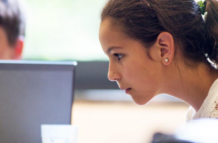 Eine Teilnehmerin arbeitet konzentriert am Laptop