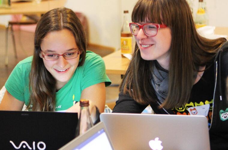 Eine Mentorin mit einer Teilnehmerin vor ihren Laptops.