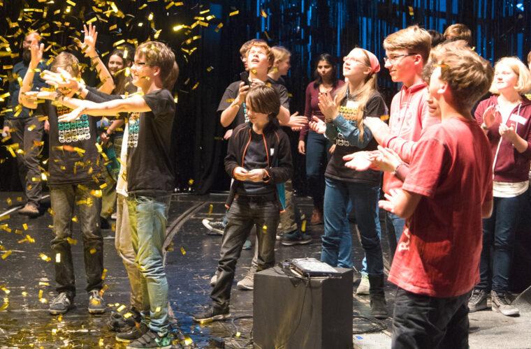 Jugendliche bei der Abschlussveranstaltung auf der Bühne mit Konfetti