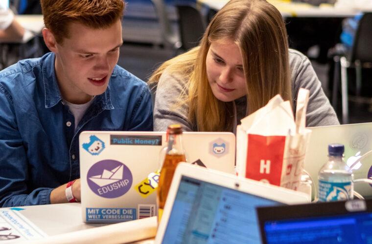 Eine Teilnehmerin und ein Teilnehmer arbeiten zusammen an ihren Laptops.