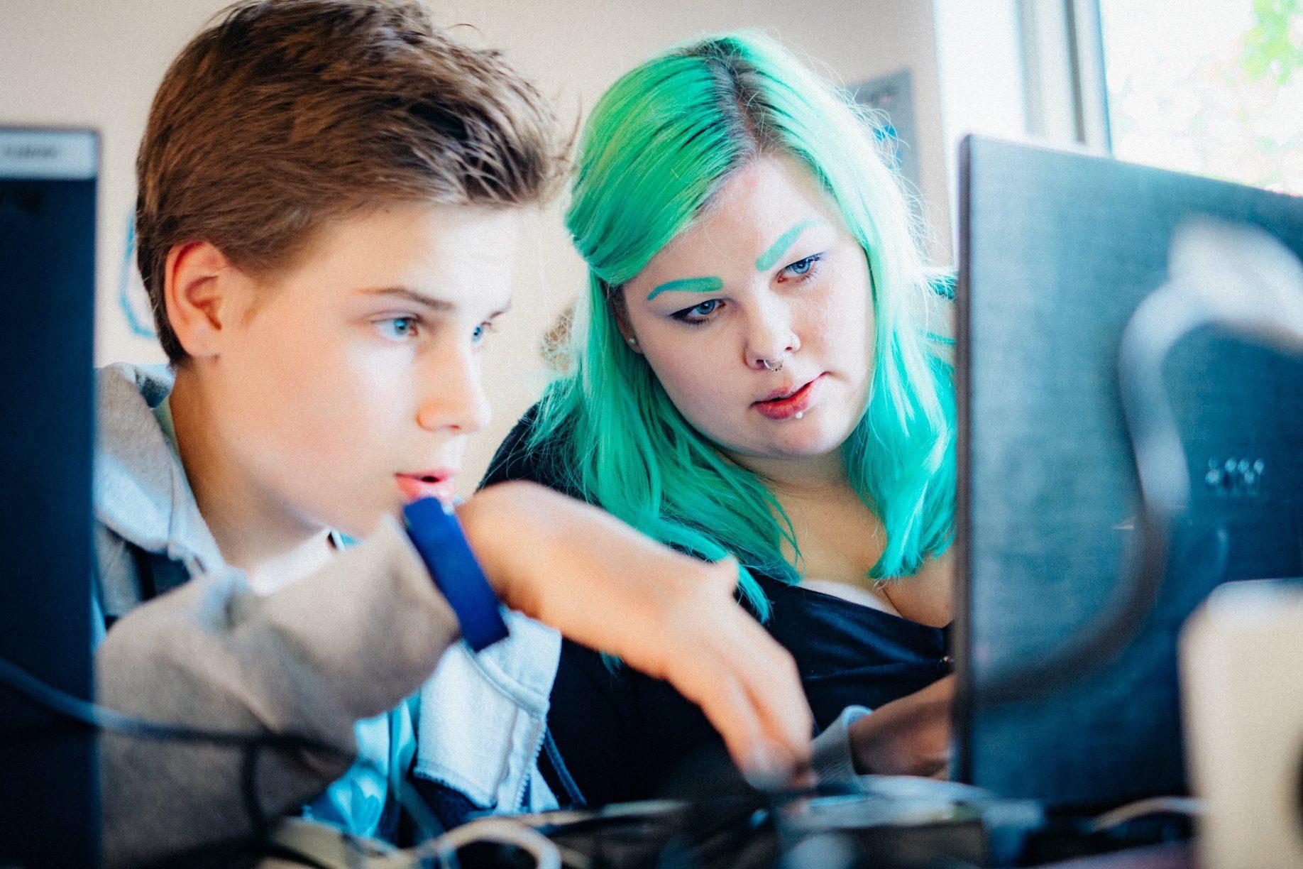 Eine Mentorin und ein Teilnehmer vor ihren Laptops.