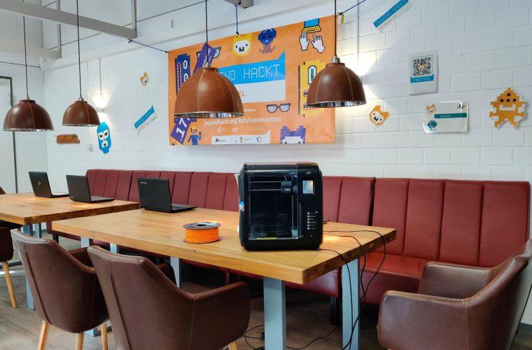 Zwei große Tische mit Sesseln und couch, darauf Laptops und 3D-Drucker. Im Hintergrund hängt ein Oranges Jugend hackt Plakat