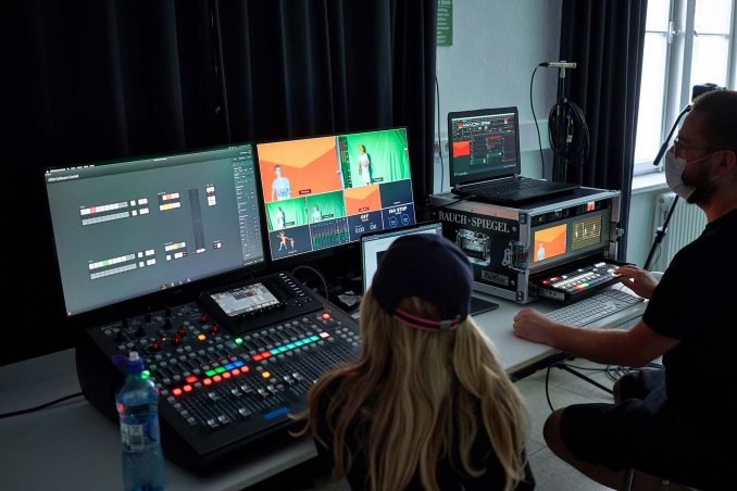 Zwei Menschen sitzen vor Equipment für Videoaufzeichnung: Monitore, Mischpulte und weitere Geräte.