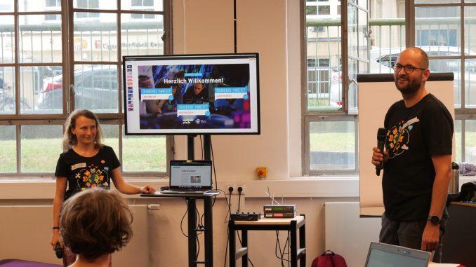 Ein Mann und eine Frau stehen vor Publikum, zwischen ihnen steht ein Bildschirm mit einer Präsentation.
