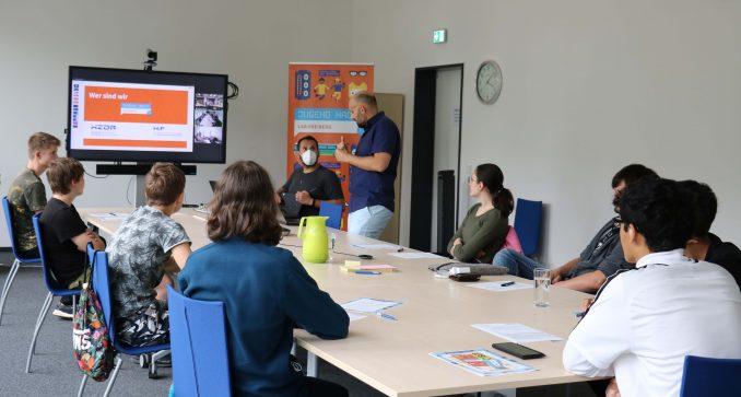 Ein Raum mit einem langen Tisch, an dem etwa zehn Menschen sitzen. Vorne erklärt eine Person etwas neben einem großen Bildschirm.